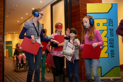 Barrierefreiheitscheck beim KiKA-Nachhaltigkeitstag: Die Kinder testen mit Augenbinden, Kopfhörern und Rollstühlen auf Barrierefreiheit.