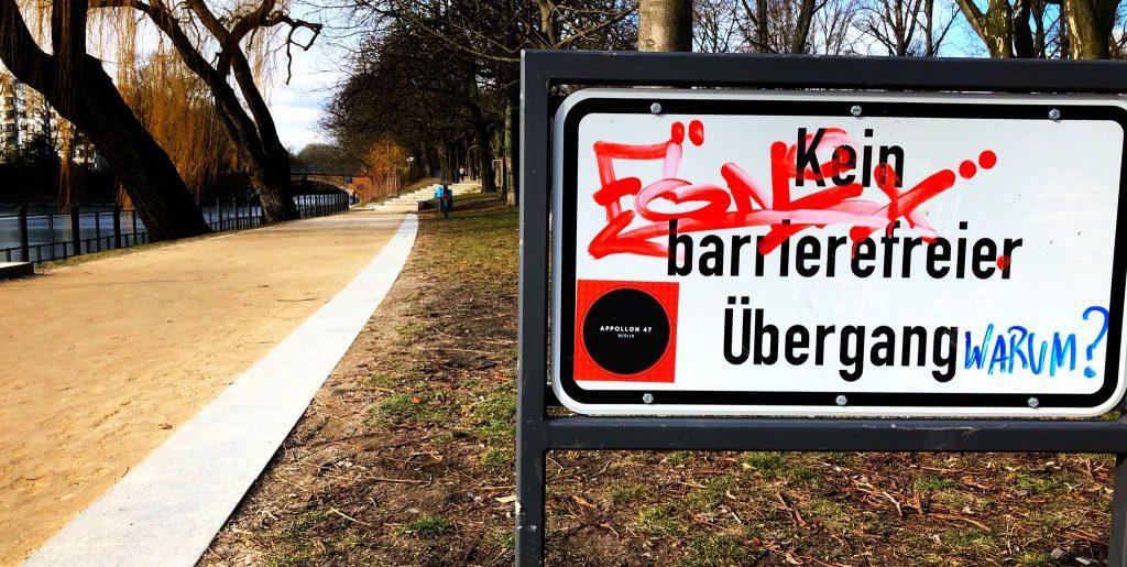 """Schild mit der Aufschrift: """"Kein Barrierefreier Übergang. Warum?"""""""