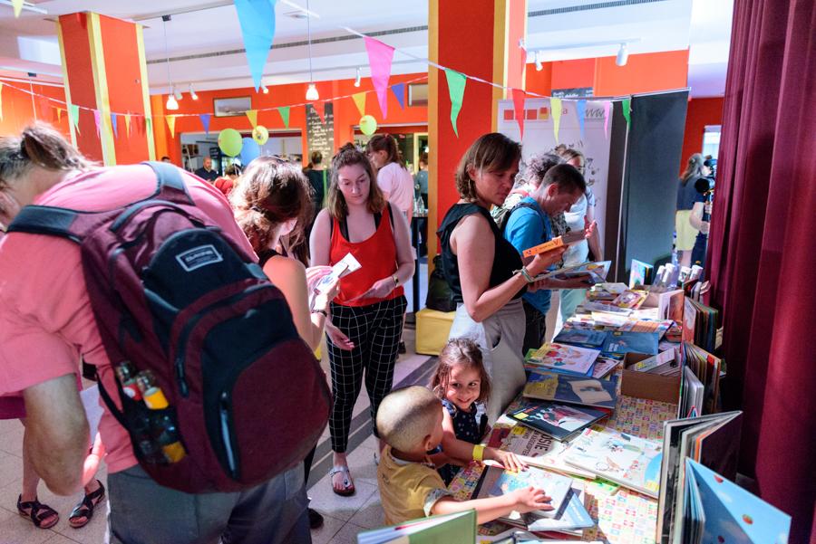 Erwachsene und Kinder schauen sich Bücher an einem Büchertisch an, im Hintergrund weitere Menschen. Vorurteilsbewusste Kinderbücher am Büchertisch des ISTA