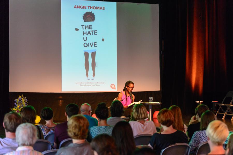 """Joana Adu-Gyamfi liest ein Buch vor einem Publikum vor, auf einer Leinwand hinter ihr sieht man ein Buch-Cover """"The Hate U Give"""" von Angie Thomas"""