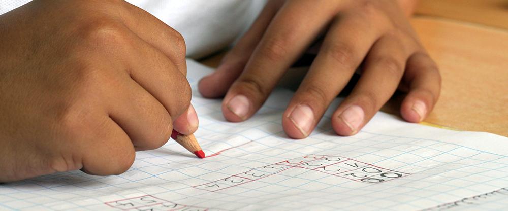 Kinderhände schreiben Zahlen auf ein Papierblatt