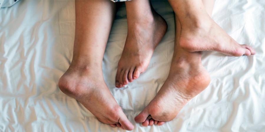 Beine gucken unter einer Bettdecke hervor
