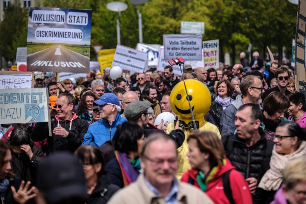 Bild von einer Demonstration bei der verschiedene Plakatae zu Inklusion hochgehalten werden.