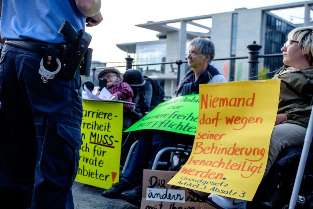 Aktivist*innen im Rollstuhl haben sich angekettet und im Hintergrund sieht man das Kanzleramt. Im Vordergrund die Handschellen von einem Polizisten.